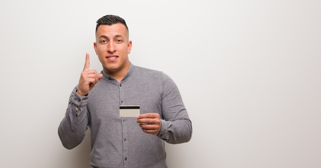 Young latin man holding a cit card showing number one