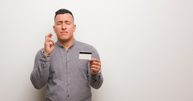 Young latin man holding a credit card crossing fingers for having luck