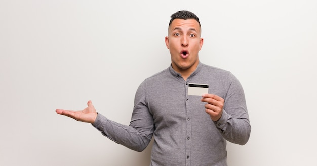 Young latin man holding a credit card holding something on palm hand