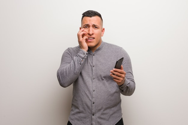 Young latin man holding a phone biting nails, nervous and very anxious