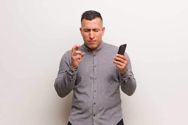 Young latin man holding a phone crossing fingers for having luck