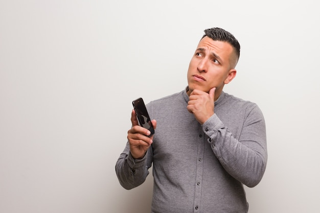 Young latin man holding a phone doubting and confused