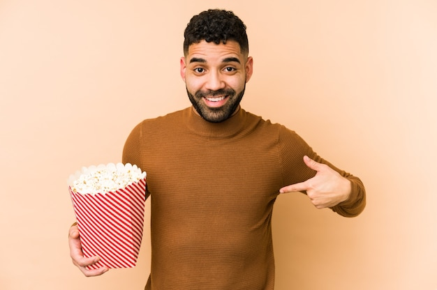 Young latin man holding a pop corn isolated person pointing by hand to a shirt copy space, proud and confident