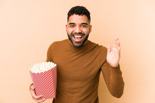 Young latin man holding a pop corn isolated receiving a pleasant surprise, excited and raising hands.