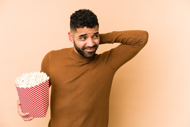 Young latin man holding a pop corn isolated touching back of head, thinking and making a choice.