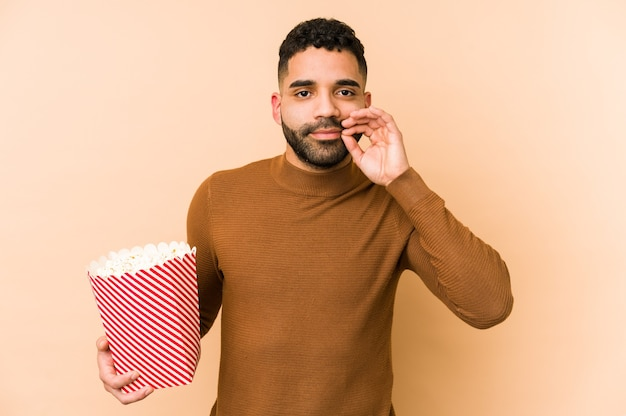 Young latin man holding a pop corn with fingers on lips keeping a secret.