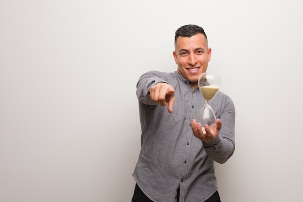 Young latin man holding a sand timer cheerful and smiling pointing to front
