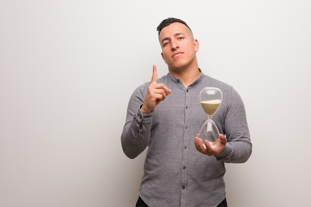 Young latin man holding a sand timer showing number one