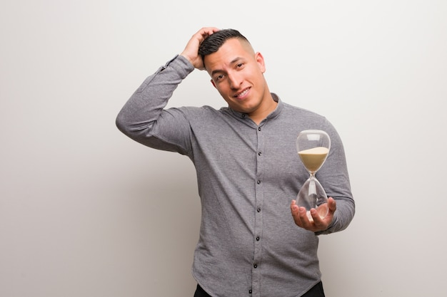 Young latin man holding a sand timer worried and overwhelmed