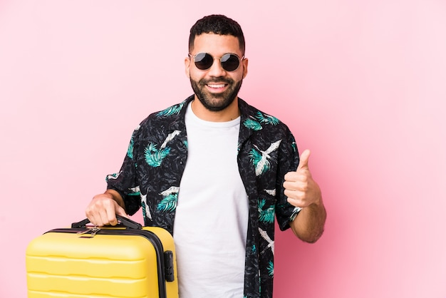 Young latin man holding a suitcase smiling and raising thumb up