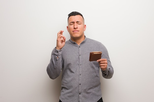 Young latin man holding a wallet crossing fingers for having luck