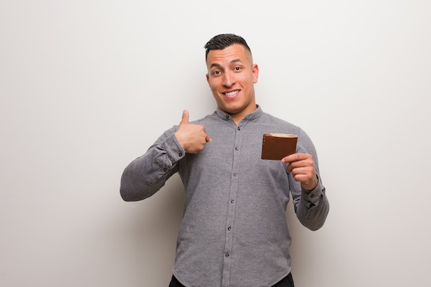 Young latin man holding a wallet surprised, feels successful and prosperous
