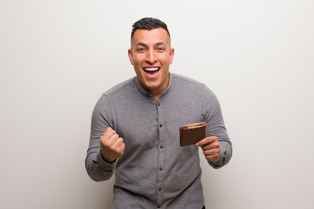 Young latin man holding a wallet surprised and shocked