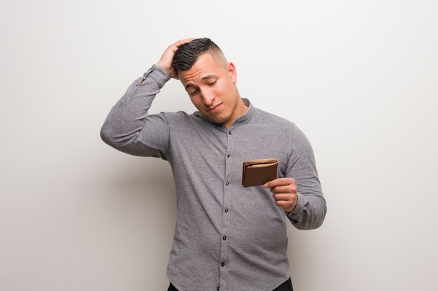 Young latin man holding a wallet worried and overwhelmed
