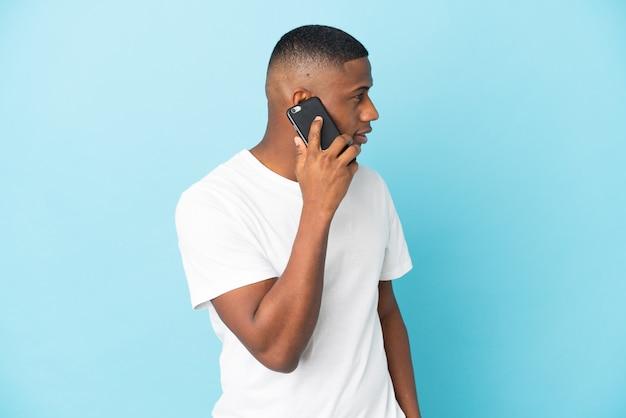 누군가와 휴대 전화로 대화를 유지하는 파란색 벽에 고립 된 젊은 라틴 남자