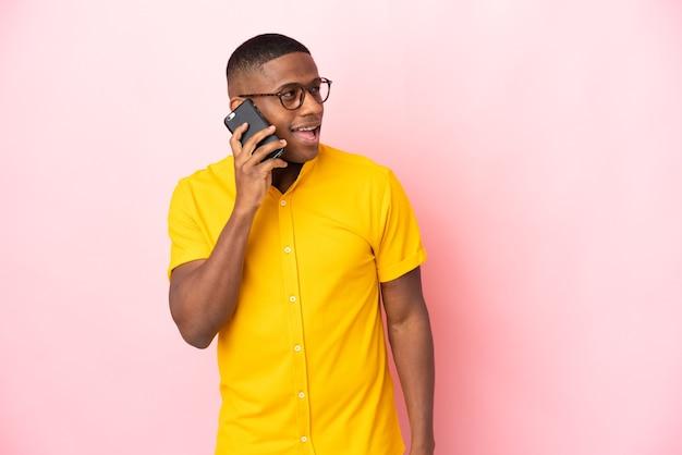 携帯電話との会話を維持しているピンクの壁に孤立した若いラテン系男性