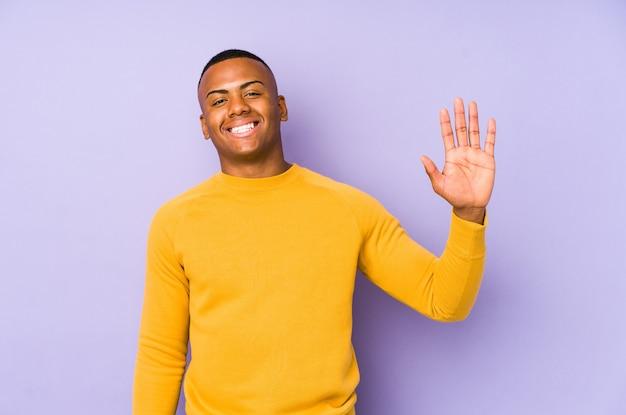 Молодой латинский человек изолирован на фиолетовой стене улыбается веселый показ номер пять с пальцами.