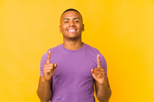 黄色の背景に分離された若いラテン系男性は、両方の前指で空白のスペースを示していることを示しています。
