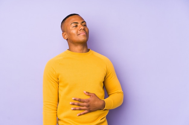 Young latin man isolated on purple touches tummy, smiles gently, eating and satisfaction concept.
