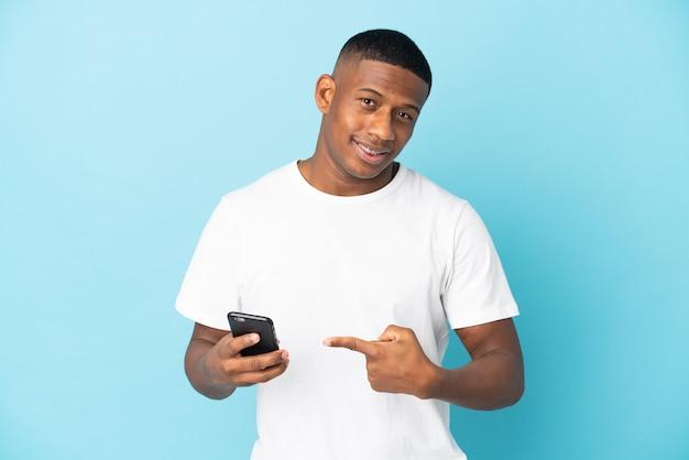 Молодой латинский мужчина изолировал с помощью мобильного телефона и указывая на него