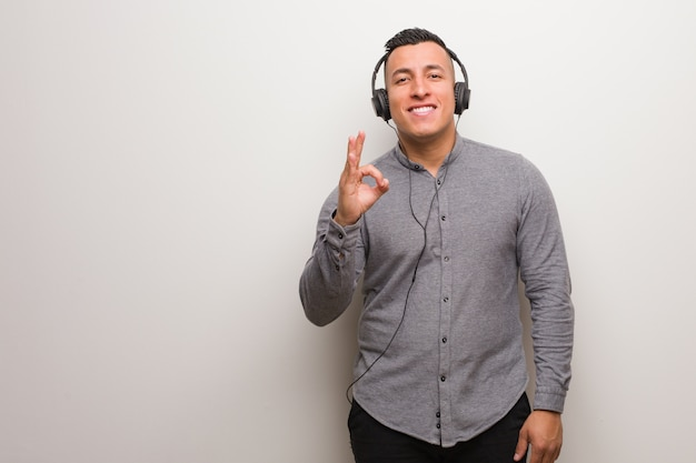 Young latin man listening to music cheerful and confident doing ok gesture