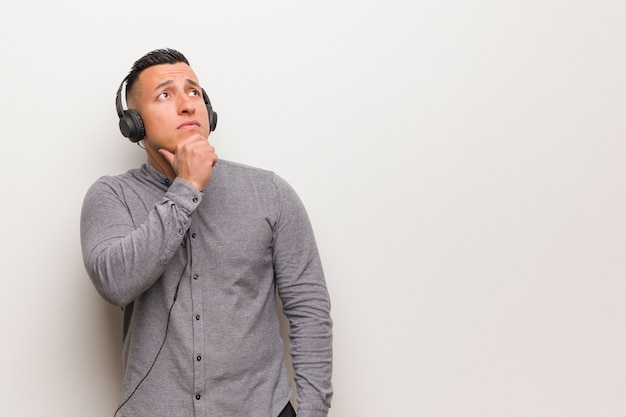 Young latin man listening to music doubting and confused