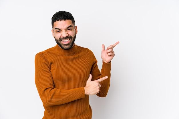 Молодой латинский человек на белом изолирован, указывая указательными пальцами на пространство для копирования, выражая волнение и желание.