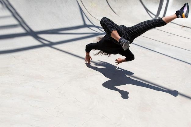 スケートピット内でストリートダンスを行う若いラテン系男性。