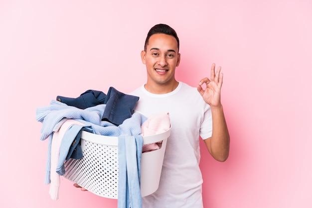 汚れた服を拾う若いラテン男は、明るく自信を持ってokジェスチャーを示します。