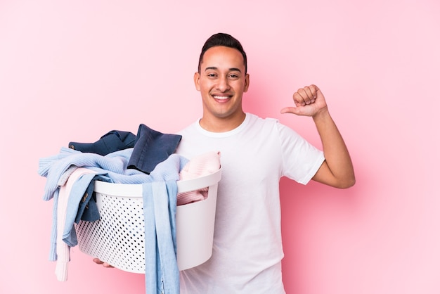 Young latin man picking up dirty clothes isolated feels proud and self confident, example to follow.