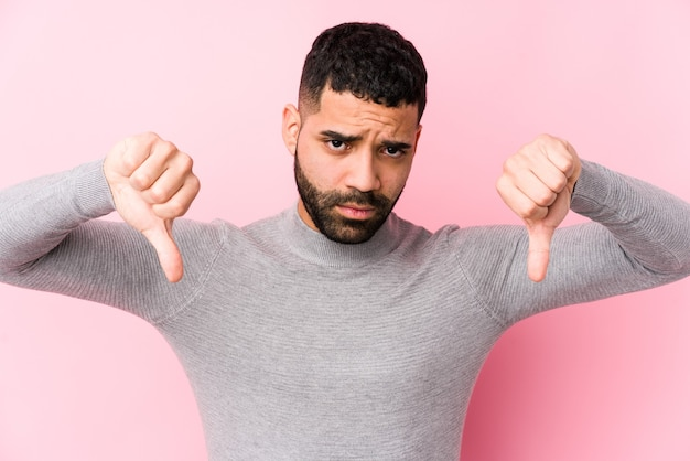 Young latin man on pink isolated showing thumb down and expressing dislike.
