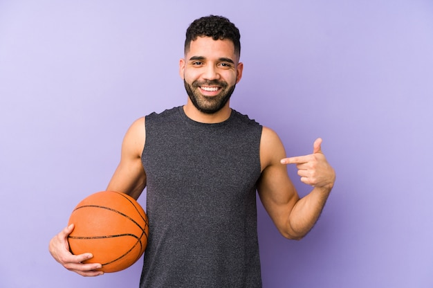 Молодой латинский мужчина играет в корзину, изолированный человек, указывая рукой на пространство для копирования рубашки, гордый и уверенный