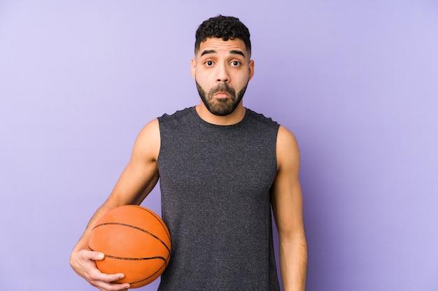 バスケットを遊んでいる若いラテン男は肩をすくめ、開いた目は混乱しています。