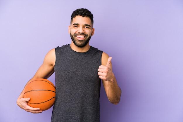 Молодой латинский мужчина играет в корзину изолирован, улыбаясь и поднимая палец вверх