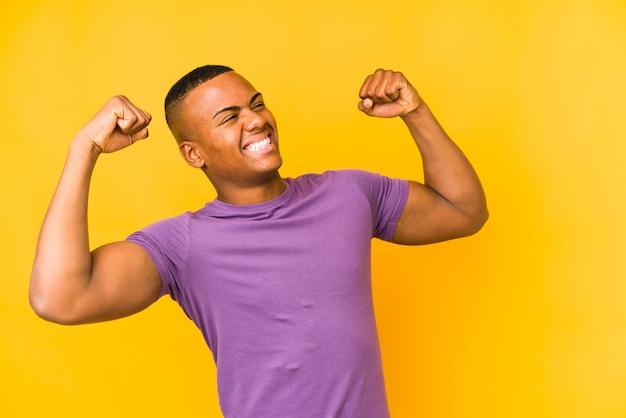 Молодой латинский человек поднимает кулак после победы, концепции победителя.