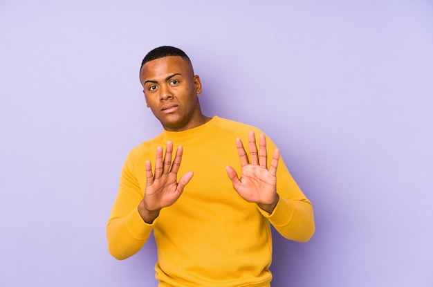 Young latin man rejecting someone showing a gesture of disgust.