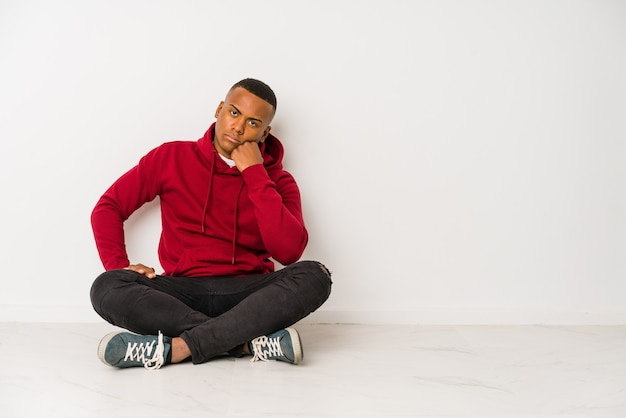 Молодой латинский человек, сидящий на полу, изолирован, который чувствует себя грустным и задумчивым, глядя на пространство для копирования.