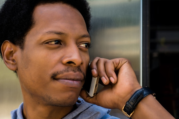 Young latin man talking on mobile phone outside.