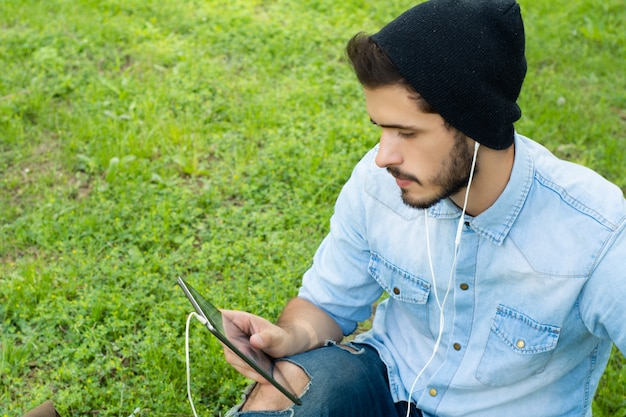 Young latin man using tablet outdoors.