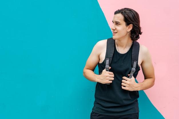 Молодой латинский человек ждет стоя с рюкзаком треккинга. фон цветной.