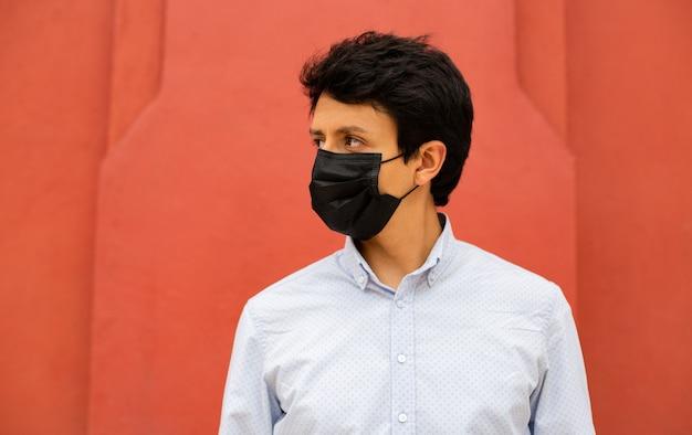 パンデミック時の保護上の理由でフェイスマスクを着用している若いラテン系男性