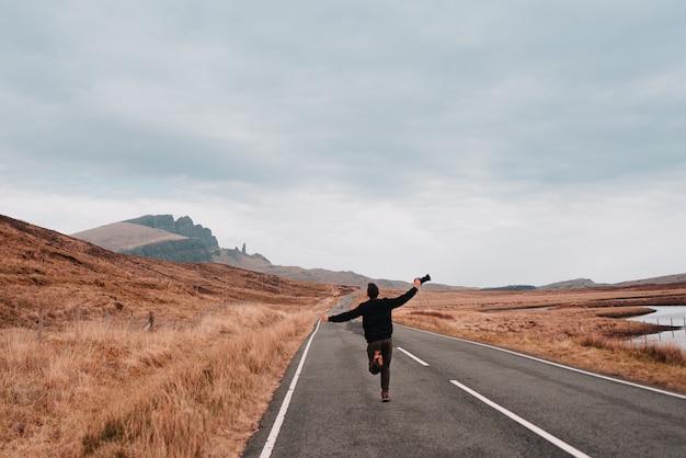 Молодой латинский мужчина с распростертыми объятиями, держит фотоаппарат и бежит посреди одинокой дороги в горы шотландии.