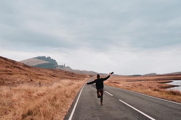 Young latin man with his arms open, holding a camera and running in the middle of a lonely road to the mountains of scotland.