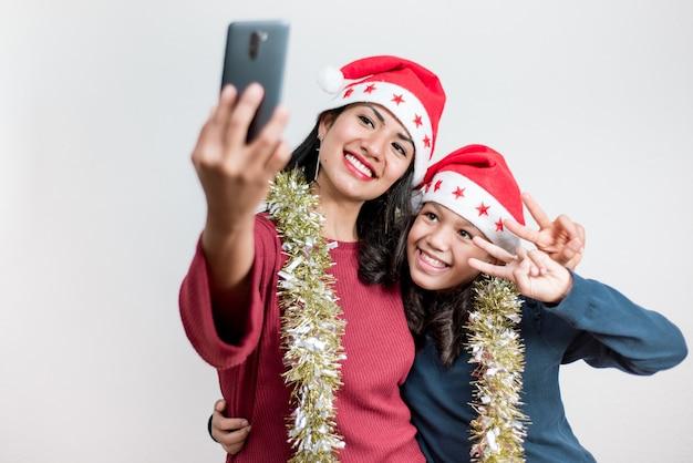 クリスマスの帽子をかぶってスマートフォンでselfieを取り、手でvサインをしている若いラテン系の母と娘。