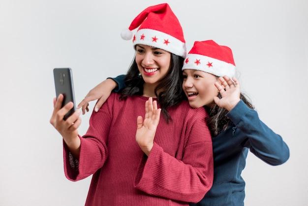 若いラテン系の母と娘はクリスマスの帽子をかぶって、クリスマスに家族とオンラインでビデオ通話をします。社会的な距離でクリスマスを祝う。