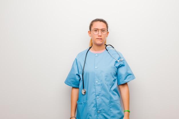 Молодая латинская медсестра, чувствуя себя невежественной, растерянной и неуверенной в том, какой вариант выбрать, пытается решить проблему с белой стеной