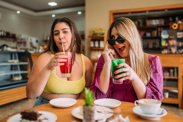 Молодые латинские большие девушки сидят в кафе и слушают забавную историю жизни своего друга