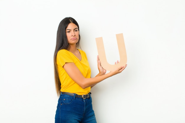 Young latin pretty woman sad, depressed, unhappy, holding the letter u