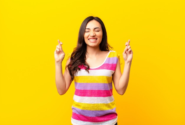 Young latin pretty woman smiling and anxiously crossing both fingers, feeling worried and wishing or hoping for good luck against flat wall