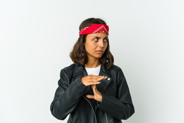 Young latin rocker woman isolated on white background frowning face in displeasure, keeps arms folded.
